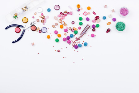 Glass, seed beads and felted beads for jewelrymaking on white background. Hobby, handmade, fine arts. Top view. Stock Photo