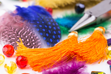 Jewelry making and beading components, glass beads, colored feathers, tassel earings,pliers on white background. Selective focus. Stock Photo