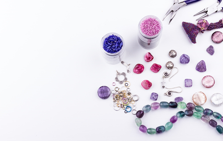 Jewelry making and beading process. Glass seed and bugle beads, amethyst and turmaline stones, silver toggle, metal beads, shell rose beads, earings, metal rings and pliers on white background. Hobby, handmade,fine arts. Top view. Stock Photo