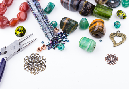 Stone beads, crystals, glass beads, metal components and seedbeads for making jewelry. Selective focus.