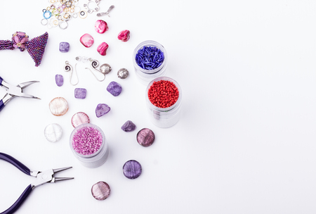 Glass seed and bugle beads, amethyst and turmaline stones, silver toggle, metal beads, shell rose beads, earings, metal rings and pliers for jewelry making and beading  on white background. Top view. Space for text.