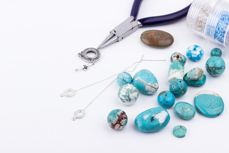 Jewelry making and beading process. Glass seed beads, turquoise stones, silver toggle, earings and pliers on white background. Hobby, handmade,fine arts. Selective focus.