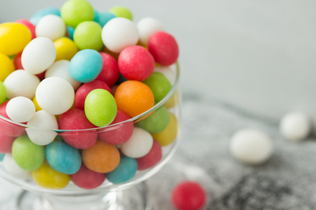 Candies in glass jar on grey background closeup. Sweet gift for special occasion: wedding, birthday, baby shower and others. Selective focus.