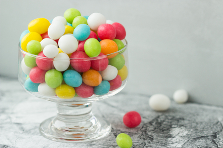 Colored candies mix in glass jar on grey background. Sweet gift for special occasion. Selective focus. Stock Photo