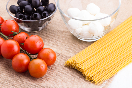 macarrones: Italian food ingredients: spaghetti,tomatoes,olives,mozzarella on white rustic wooden background. Selective focus.