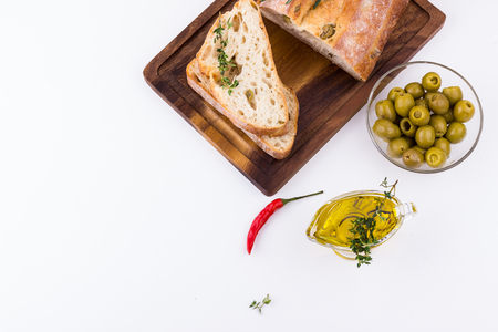Ciabatta bread with green olives, olive oil, rosemary, red chili pepper, on wooden cutting board on white background. Selective focus. Top view.