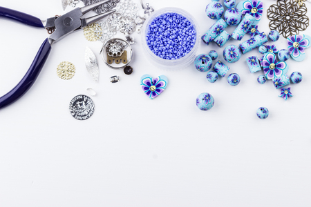 Jewelry making and beading. Seedbeads, metal components, polyclay purple blue flower beads mix, pliers on white background. Selective focus. Top view.
