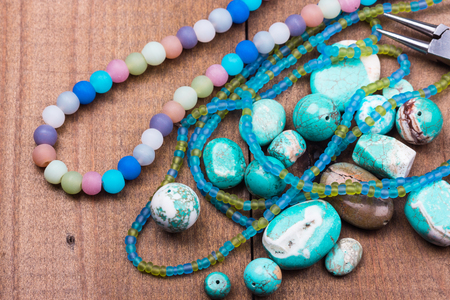Turquoise gemstones, colorful glass beads, seedbeads, gemstones mix closeup on wooden background. Selective focus.