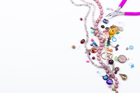 Mix of glass and seed beads, gemstone beads, metal findings, pliers for beading hobby on white background. Selective focus. Top view.