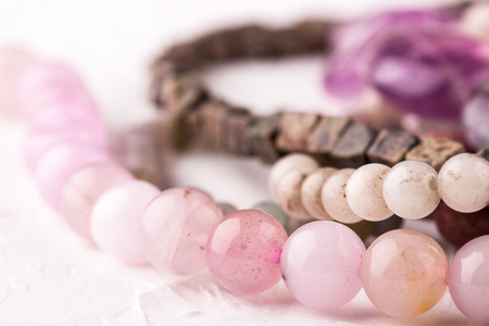 Rose quartz stone beads on white background closeup. Selective focus.