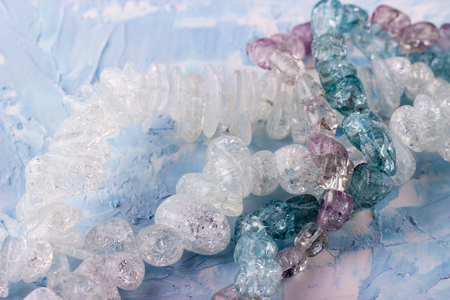 Gemstone crystal bead mix for winter handmade on blue background. Closeup. Selective focus.