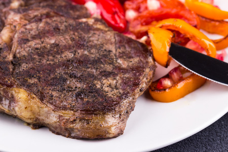 Grilled beef steak on a white plate on grey background. Closeup. Selective focus. Stock Photo