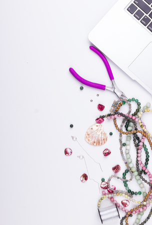 Handmade, hobby, craft workspace concept. Feminine workplace in flat lay style with laptop and materials for handmade jewelry making. Gemstone beads, shell beads, heart-shaped shell findings, earrings, pliers and thread on white background. Space for text. Top view. Stock Photo