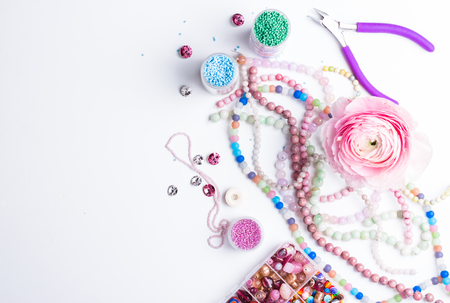 Glass seed beads, gemstones, crystals, pliers and rose flower on white background. Hobby, handmade, fine arts. Flat lay. Space for text.