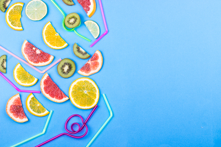Flat lay summer coctail concept. Citrus slices and straws on blue background. Flat lay. Space for text. Stockfoto