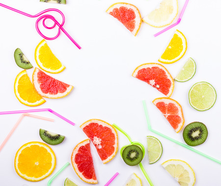 Summer coctail concept. Citrus slices and straws on white background. Flat lay. Space for text. Stock Photo