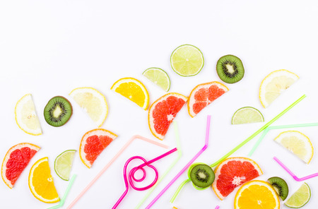 Flat lay citrus slices and straws for summer coctails on white background. Space for text.