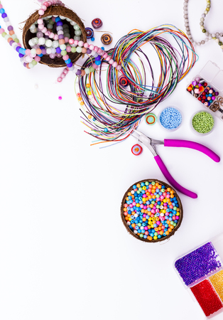 Feminine workplace in flat lay style. Gemstone and glass beads, materials for handmade jewelry making on white background.