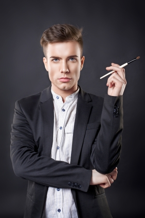 gigolo: Stylish young handsome man in a suit with a brush