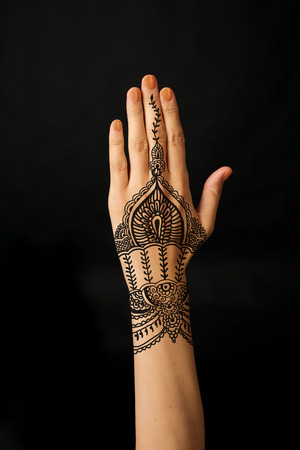 hand with mehendi on black background photo