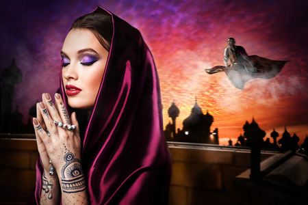 fashion story: Woman praying in the desert with mehendi on hands and wearing the hijab Stock Photo
