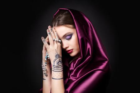 maquillaje de ojos: hermosa mujer en estilo oriental con mehendi en hijab Foto de archivo