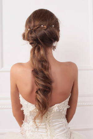 bridal hair: beautiful girl the bride on a background of bright stucco