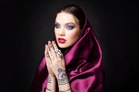 hijab: beautiful woman in oriental style with mehendi in hijab