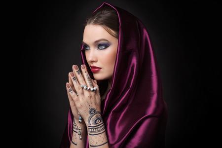 arab model: beautiful woman in oriental style with mehendi in hijab