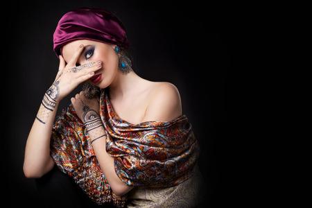 beautiful woman in oriental style with mehendi in hijab