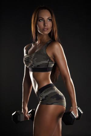 sudoracion: fuerte chica hermoso deporte morena sobre un fondo negro. copiar el espacio. Foto de archivo