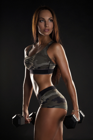 gym girl: strong tanned beautiful sports girl on a black background. copy space. Stock Photo