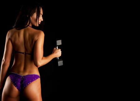 black girl: Durchtrainiert Muskul�s Sch�ne sportliche Frau mit einer Hantel auf einem dunklen Hintergrund. kopieren Sie Platz.