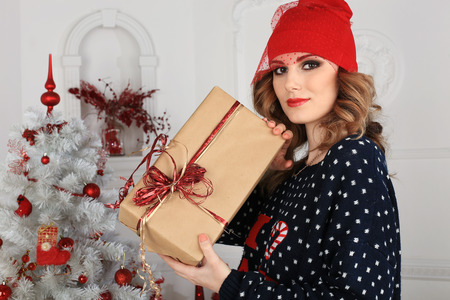 sweater girl: beautiful woman gives a gift  Christmas theme Stock Photo