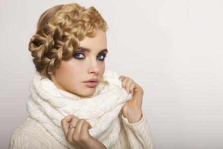 sweater girl: portrait of a beautiful young blonde woman on a light background. hair tied in a braid. girl wearing a warm sweater and scarf. copy space.