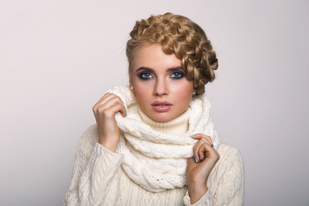 tied girl: portrait of a beautiful young blonde woman on a light background. hair tied in a braid. girl wearing a warm sweater and scarf. copy space.