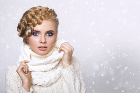 winter wedding: portrait of a beautiful young blonde woman on a light background. hair tied in a braid. girl wearing a warm sweater and scarf. copy space.