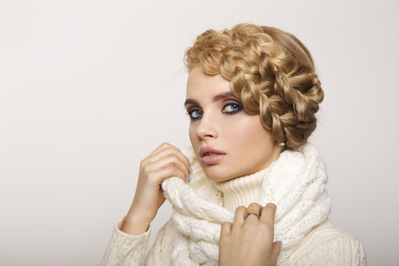 winter fashion: portrait of a beautiful young blonde woman on a light background. hair tied in a braid. girl wearing a warm sweater and scarf. copy space.