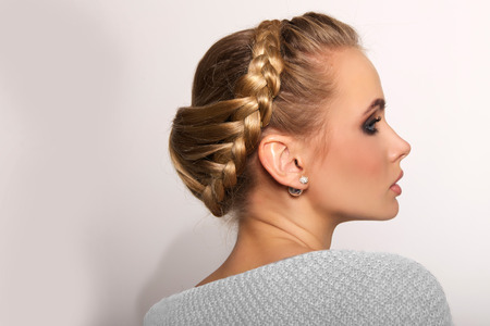 blond hair: portrait of a beautiful young blonde woman on a light background with hairdo on her head. copy space.