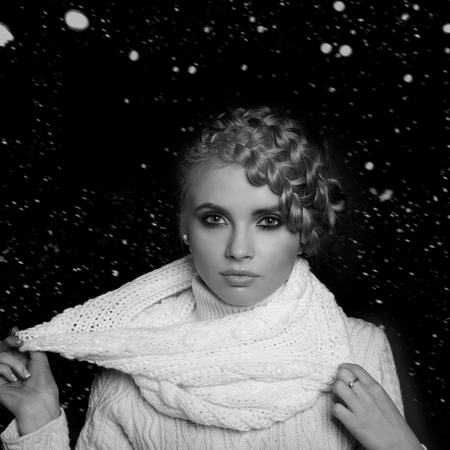 fall winter: portrait of a beautiful young blonde woman on dark background with snow. hair tied in a braid. girl wearing a warm sweater and scarf. copy space.