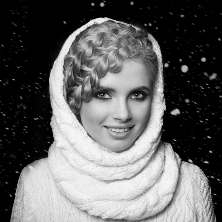 tied girl: portrait of a beautiful young blonde woman on dark background with snow. hair tied in a braid. girl wearing a warm sweater and scarf. copy space.