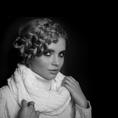 hair tied: portrait of a beautiful young blonde woman on dark background. hair tied in a braid. girl wearing a warm sweater and scarf. copy space.