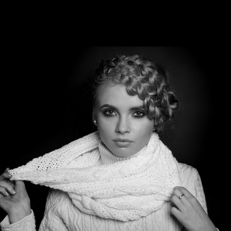 tied in: portrait of a beautiful young blonde woman on dark background. hair tied in a braid. girl wearing a warm sweater and scarf. copy space.