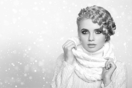 hair tied: portrait of a beautiful young blonde woman on a light background. hair tied in a braid. girl wearing a warm sweater and scarf. copy space.