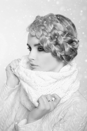 tied in: portrait of a beautiful young blonde woman on a light background. hair tied in a braid. girl wearing a warm sweater and scarf. copy space.