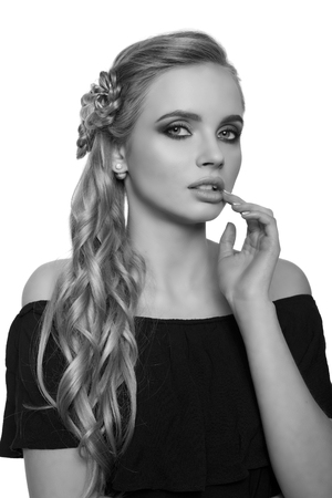 chignon: portrait of a beautiful young blonde woman on a light background with hairdo on her head. copy space.