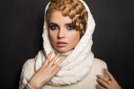 gefesselt: Porträt einer schönen jungen blonden Frau auf dunklem Hintergrund. Haar in einem Zopf gebunden. Mädchen, das einen warmen Pullover und Schal. Kopie Raum.