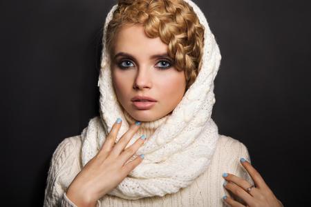 sueteres: retrato de una mujer joven rubia sobre fondo oscuro. el pelo recogido en una trenza. chica que llevaba un su�ter y bufanda. espacio de la copia.