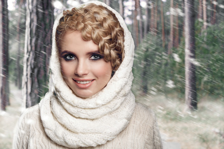 tied girl: portrait of a beautiful young blonde woman on a forest background. hair tied in a braid. girl wearing a warm sweater and scarf. copy space. Stock Photo