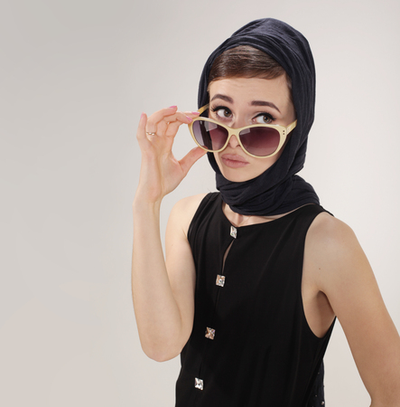 beautiful woman in retro style with headscarf and sunglasses on light background